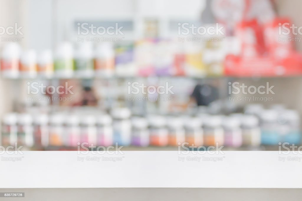 pharmacy store counter table top with blur medicine on shelves stock photo
