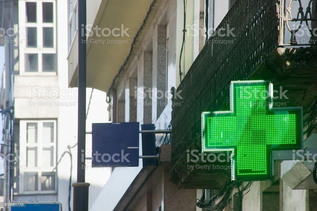 Pharmacy symbol in the street, green cross. stock photo
