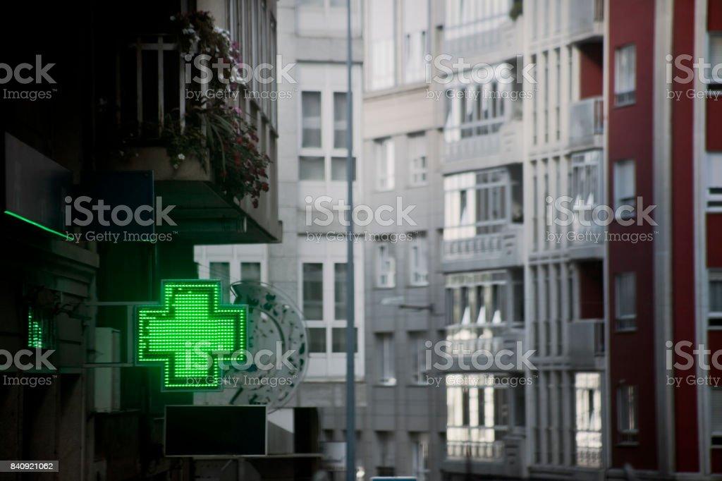 Pharmacy symbol in the street, tall buildings, green cross. stock photo