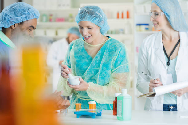pharmacy technician mixes medication in assembly line - pharmaceutical compounding stock photos and pictures