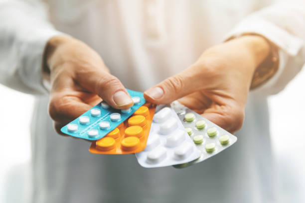 pharmacy - woman hands holding blister packs with pills pharmacy - woman hands holding blister packs with pills pill container stock pictures, royalty-free photos & images