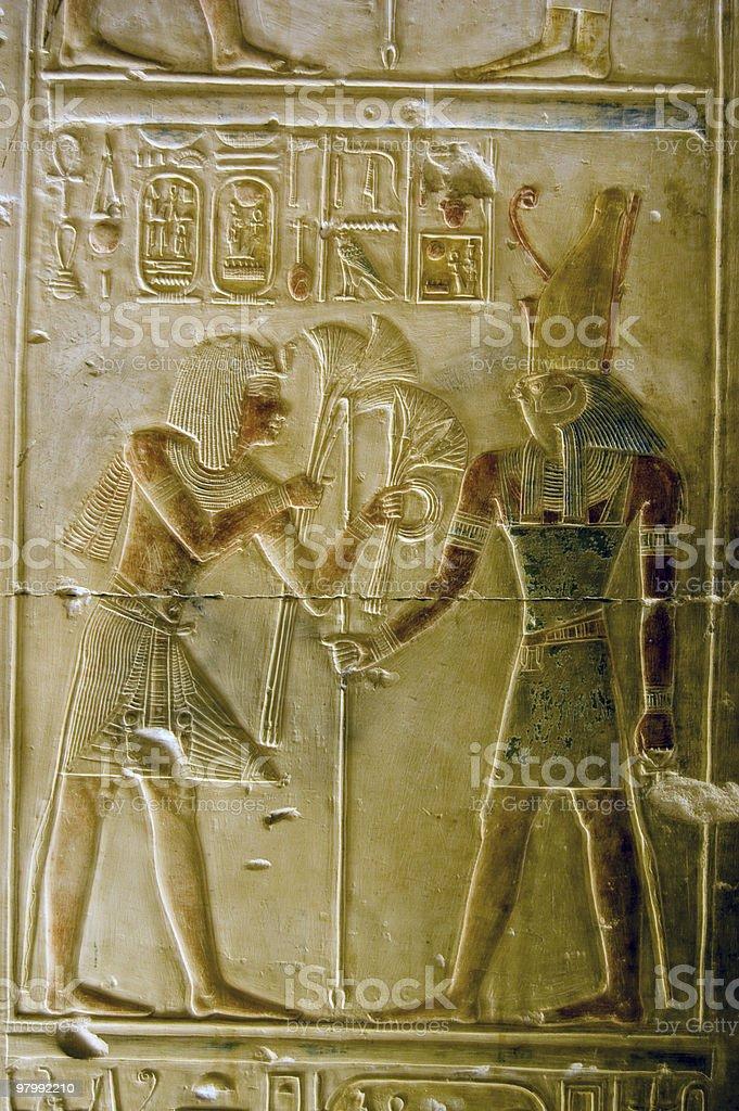 Pharoah Seti presenting lotus flowers to god Horus royalty-free stock photo