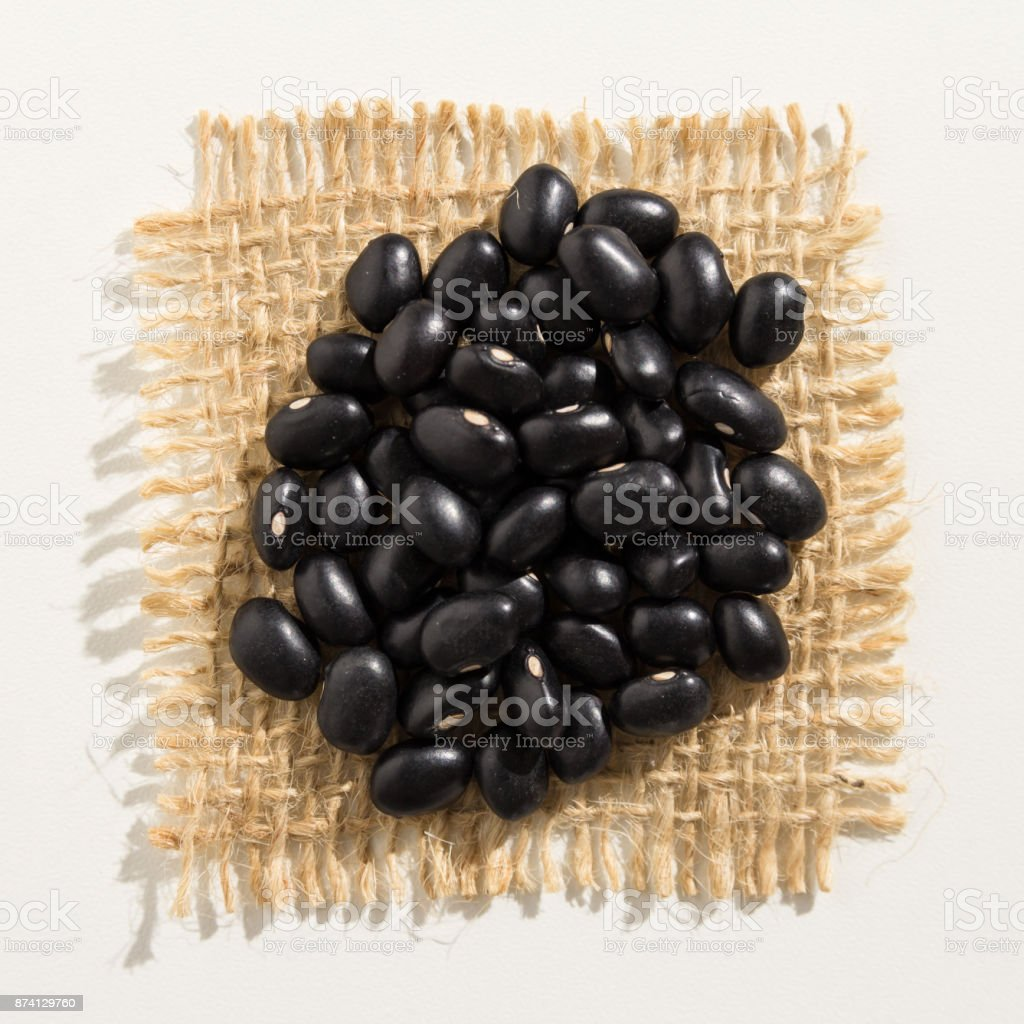Phaseolus vulgaris is scientific name of Black Turtle Bean legume. Also known as Frijoles Negros and Feijao Preto. Close up of grains over burlap. stock photo
