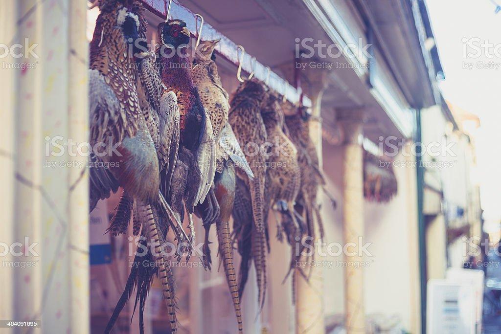 Pheasants hanging outside butcher's shop stock photo
