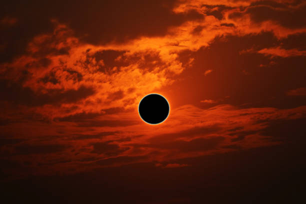 phenomenon of partial sun eclipse over silhouette orange cloud and sunset sky stock photo
