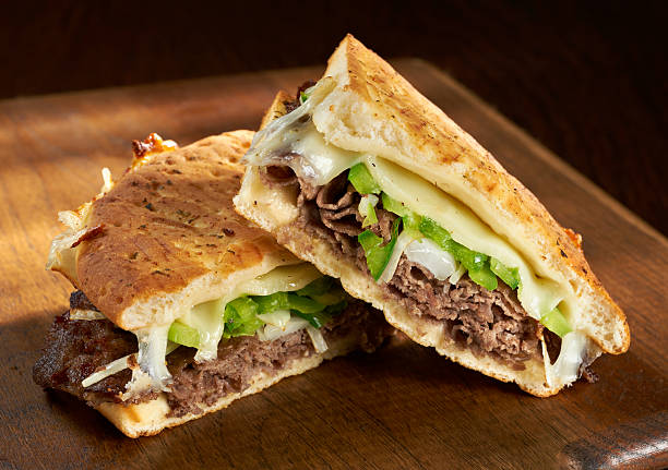 Philadelphia Cheese Steak Panini Philadelphia Cheesesteak Flatbread or Panini sandwich made with steak, provolone cheese and saute onions and bell peppers. burwellphotography stock pictures, royalty-free photos & images