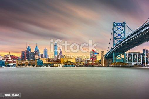 Philadelphia, Pennsylvania, USA skyline on the Delaware river with Ben Franklin Bridge at night.