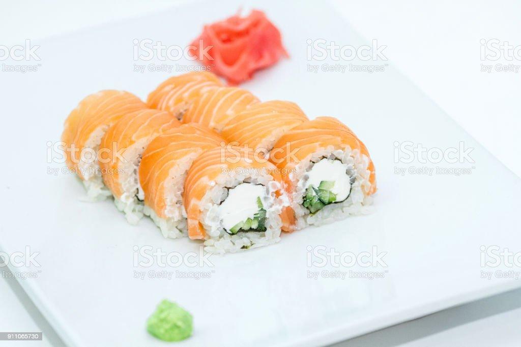 Philadelphia roll sushi with rice, nori, wasabi, soy sauce, pickled ginger, cheese, cucumber, salmon. Sushi menu. stock photo