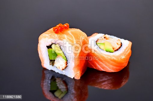 Philadelphia roll sushi with salmon, avocado, red caviar and cream cheese on black background for menu. Japanese food