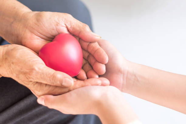 Philanthropy health care concept. Caregiver with senior people hands with heart in palm in hospice center with copyspace. Public Service Recognition Week stock photo