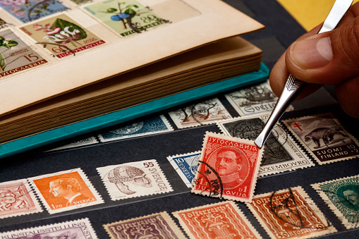 Nis, Serbia- November 20th 2020: The philatelist holds a used postage stamp with the image of the King of Yugoslavia,  Alexander I (1888-1934), using tweezers above the stamp album. Photo taken on November 20th 2020.