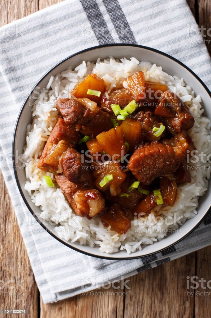 Philippine cuisine: Hamonado pork with pineapple and garnish of rice close-up. Vertical top view stock photo