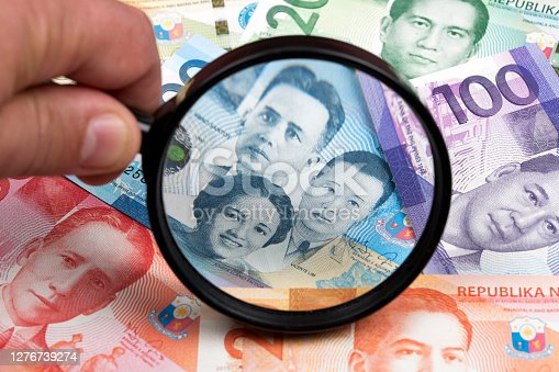 Philippine peso in a magnifying glass a business background