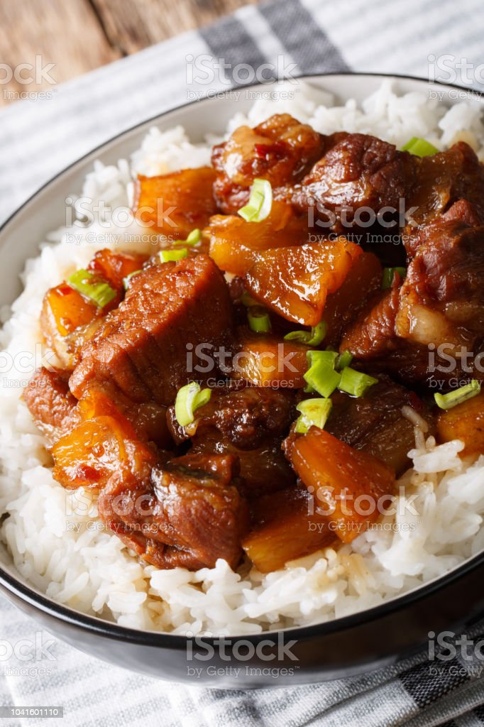 Philippine spicy pork Hamonado with pineapple and rice close-up. vertical stock photo