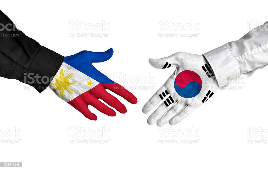Philippines and South Korea leaders shaking hands on a deal stock photo