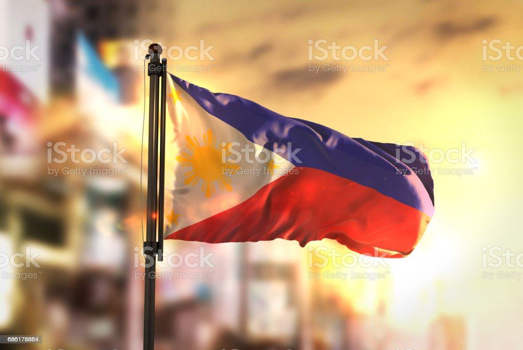 Philippines Flag Against City Blurred Background At Sunrise Backlight stock photo