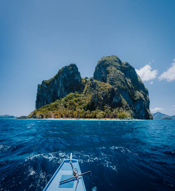 Philippino local boat facing impressive tropical Pinagbuyutan Island. El Nido, Palawan, Philippines Philippino local boat facing impressive tropical Pinagbuyutan Island. El Nido, Palawan, Philippines. pinagbuyutan island stock pictures, royalty-free photos & images