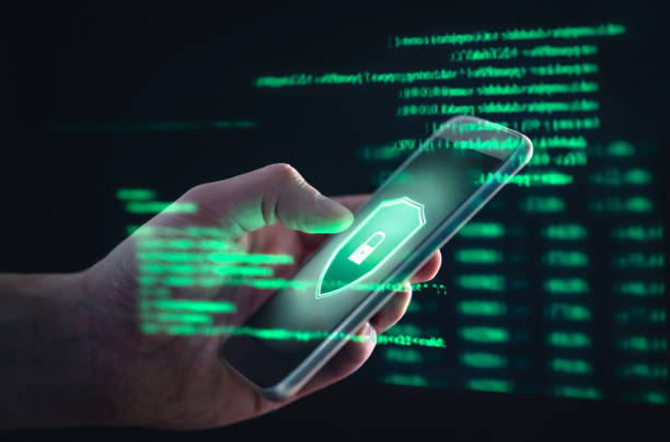 Phishing, cyber security, online information breach or identity theft crime concept. Hacked phone. Hacker and cellphone with hologram data. Mobile scam, fraud or crime. stock photo