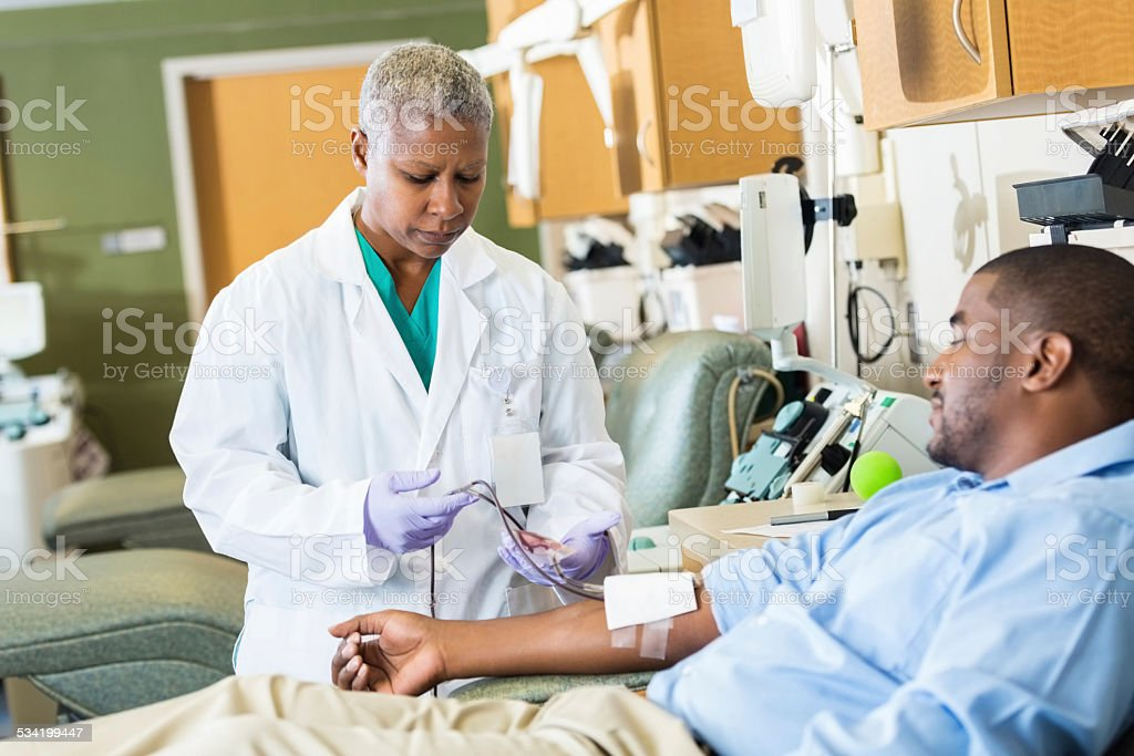 Phlebotomist checking line whle patient donates blood in hospital stock photo