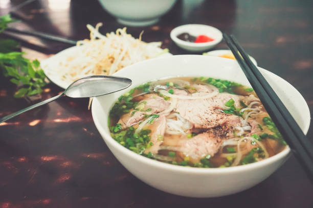 pho bo - vietnamese fresh rice noodle soup with beef, herbs and chili. vietnam's national dish. - pho soup stock photos and pictures