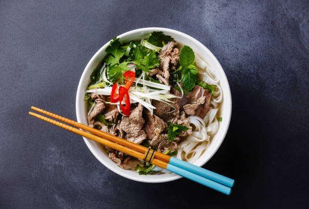 Pho Bo vietnamese Soup Pho Bo vietnamese Soup with beef on dark background rice noodles stock pictures, royalty-free photos & images
