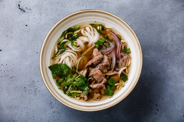 Pho Bo vietnamese Soup with beef in bowl Pho Bo vietnamese Soup with beef in bowl on concrete background rice noodles stock pictures, royalty-free photos & images