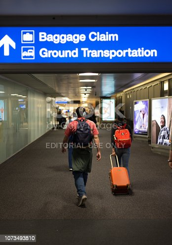 """Phoenix, AZ: Passengers with luggage walk underneath a sign at Phoenix International Airport that reads """"Baggage Claim"""" and """"Ground Transportation."""""""