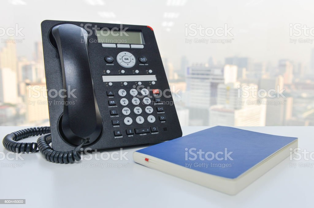 IP Phone and blue notebook on the white table - Technology of communication stock photo