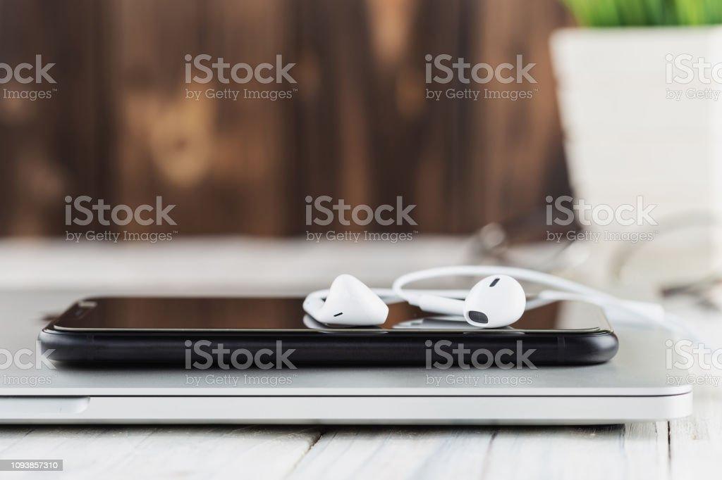 Telefon und Kopfhörer-Stack auf Laptop-Computer-Frontansicht – Foto