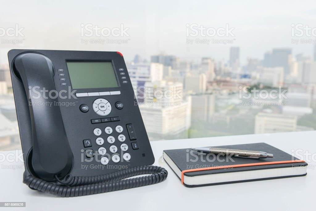 IP Phone and notebook with pen on the white office desk stock photo