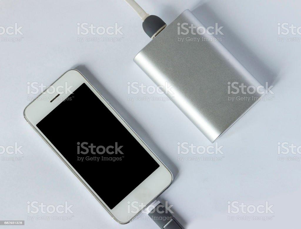 Phone and powerbank on white background foto de stock libre de derechos