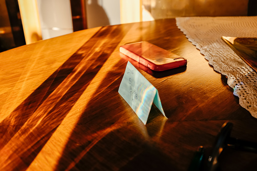 Phone and sticky note on the table in the sunlight