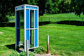 Vintage phone booth in front of a freshly cut lawn