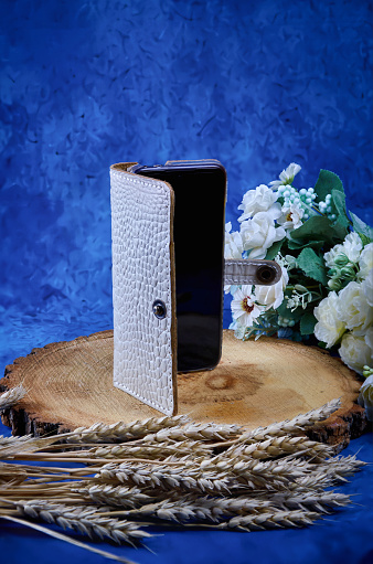 Phone case made of genuine white caiman leather, handmade, do it yourself, on a blue background