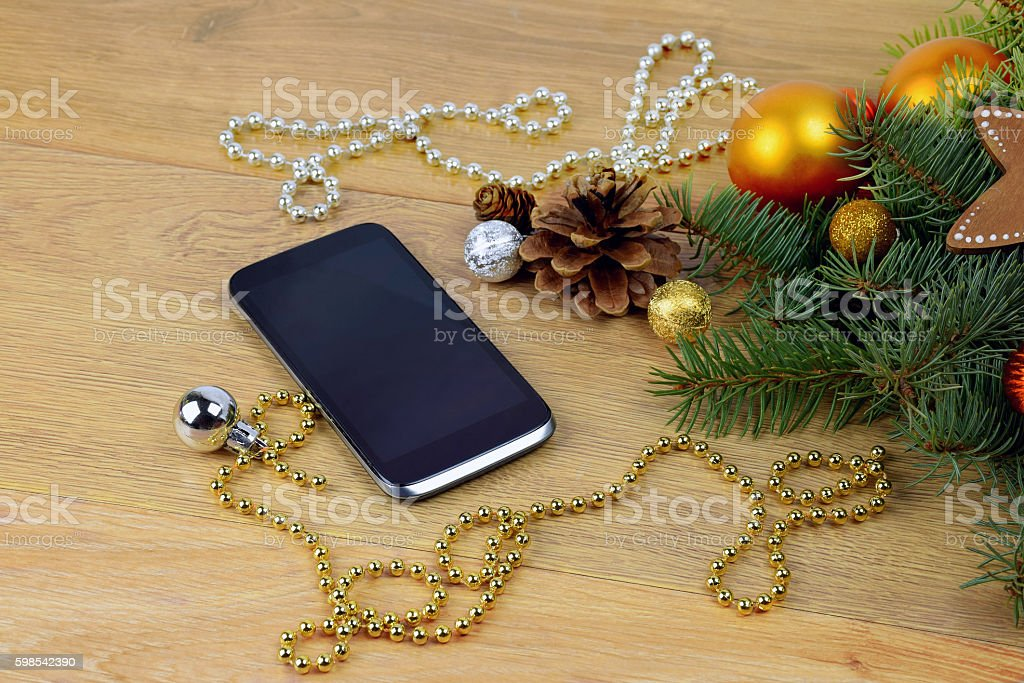 phone greetings.Smartphone and Christmas tree on wooden background. photo libre de droits