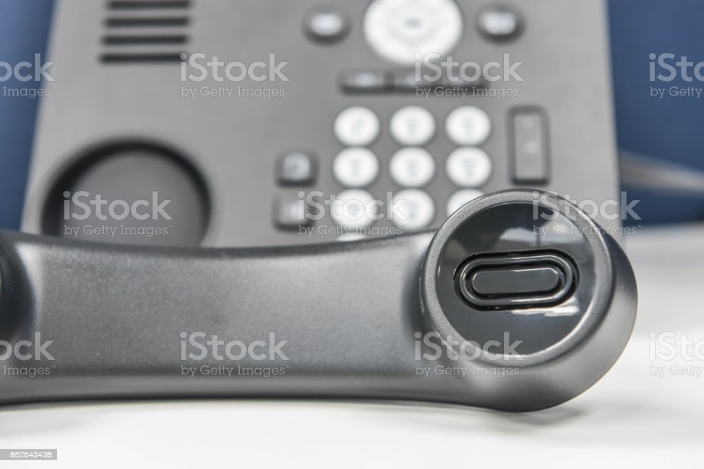 IP Phone handset is holding the call on the white table stock photo