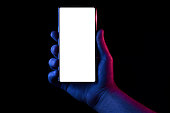 Phone in hand. Silhouette of male hand lit with blue and red neon lights holding bezel-less smartphone on black background. Screen is cut with clipping path.