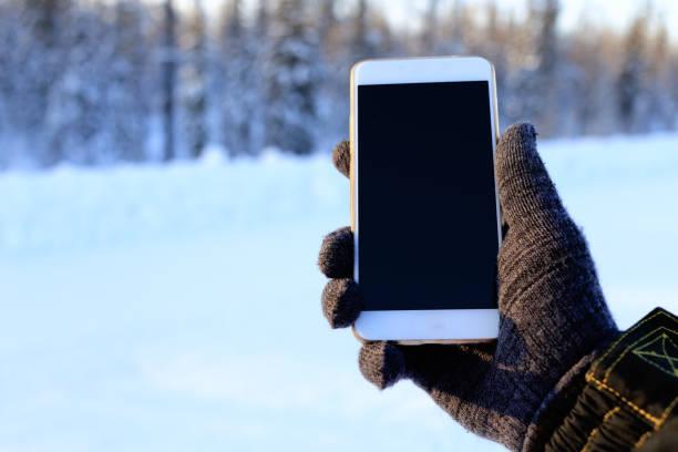 téléphone dans les mains du voyageur - paire de gants photos et images de collection