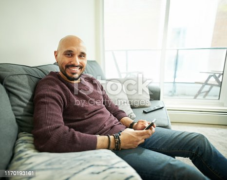 Shot of smiling young man sitting on couch with a mobile phone