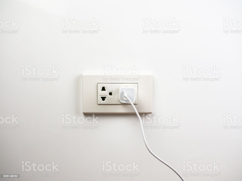 Phone plugged in on socket wall, charging stock photo