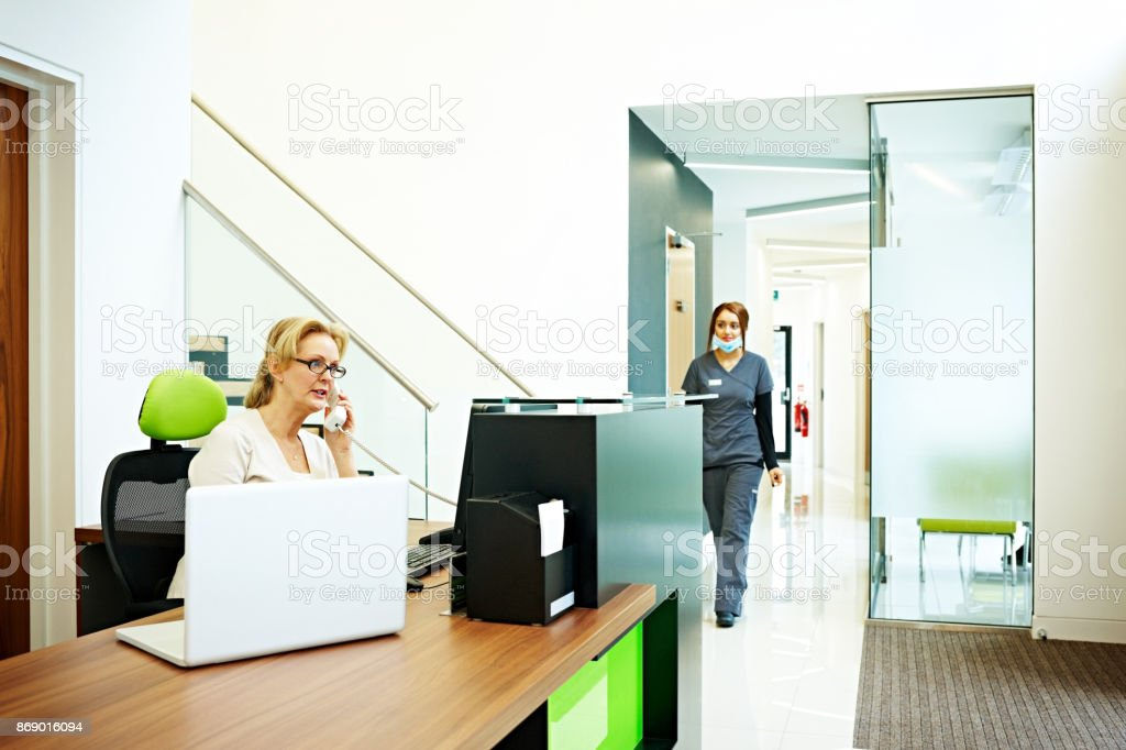 Phone Receptionist Scheduling Appointments In Dental Clinic Stock Photo