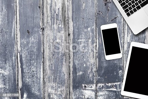 932821906 istock photo phone tablet computer on a wooden table 481651588