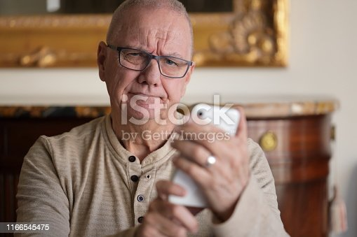 Senior man having trouble with his phone.