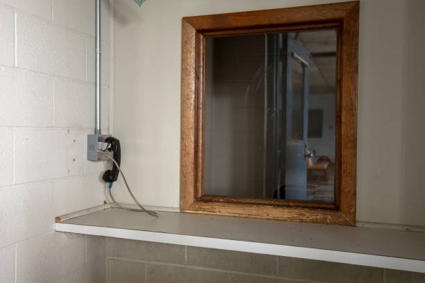 telefoon gebruikt door bezoekers op verlaten gevangenis - raam bezoek stockfoto's en -beelden