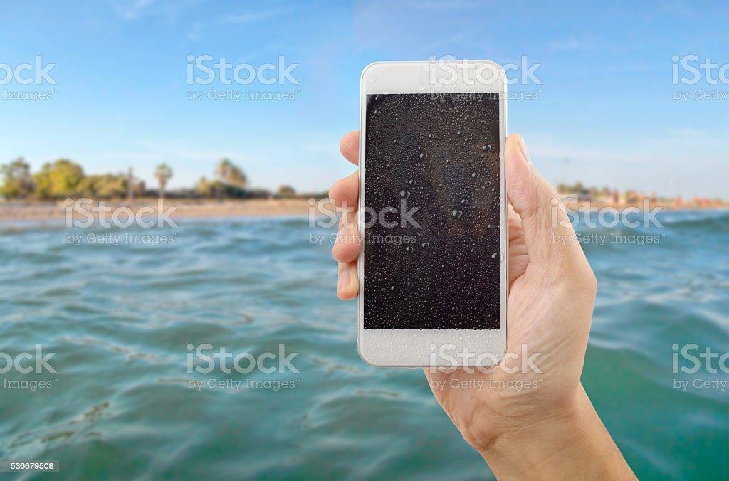 phone wet on the beach stock photo