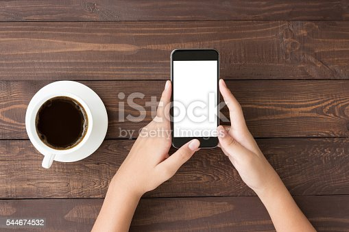 istock phone white screen in woman hand on table top view 544674532
