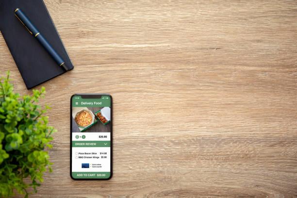 Telefon mit App Lieferfutter auf Bildschirm und Holztisch – Foto