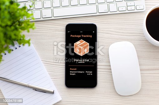 istock phone with app tracking delivery package screen in office 1003475188