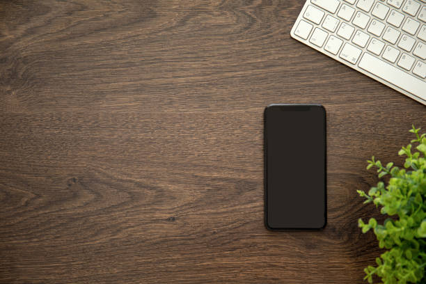 Telefon mit schwarzem Bildschirm auf Holztisch mit einer Tastatur – Foto