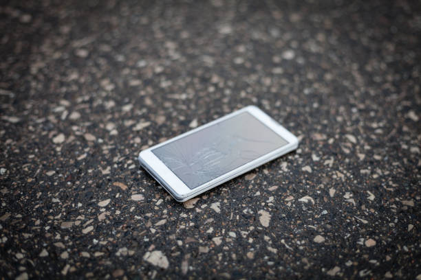 Phone with broken screen lying on the street stock photo